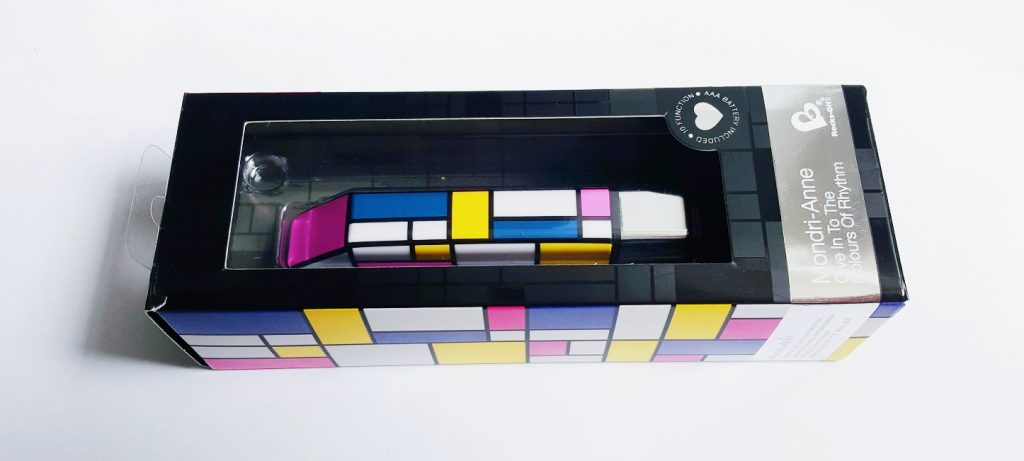 Photo of the Rocks Off Mondri-Anne Packaging. A black cardboard box with Mondrian inspired print in white, blue, yellow and pink.