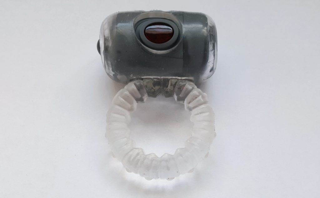 Photo of the Hera Cockring from inside the LoveDrop box. A clear ring with a grey bullet inserted and red light up sensor.