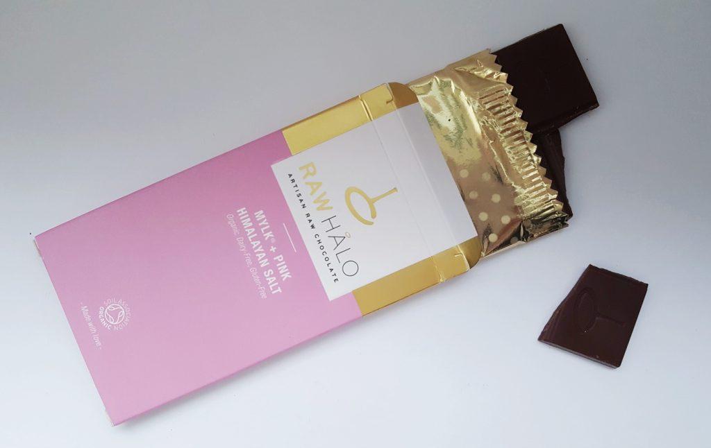 Photo of the Raw Halo Mylk Choc & Pink Himalayan Salt. A bix cradboard box with gold wrapped chocolate inside.