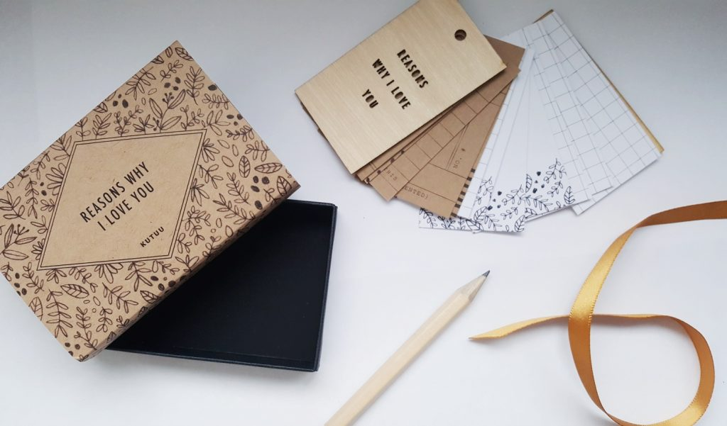 """Photo of the Kutuu """"Reasons Why I Love You"""" Tag Book. A brown cardboard box with intricate black design, small wooden pencil, coppor coloured ribbon and wooden front and back pages to book with reasons I love you laser cut from the front. Image also includes the brown and white pages for inserting into the book."""