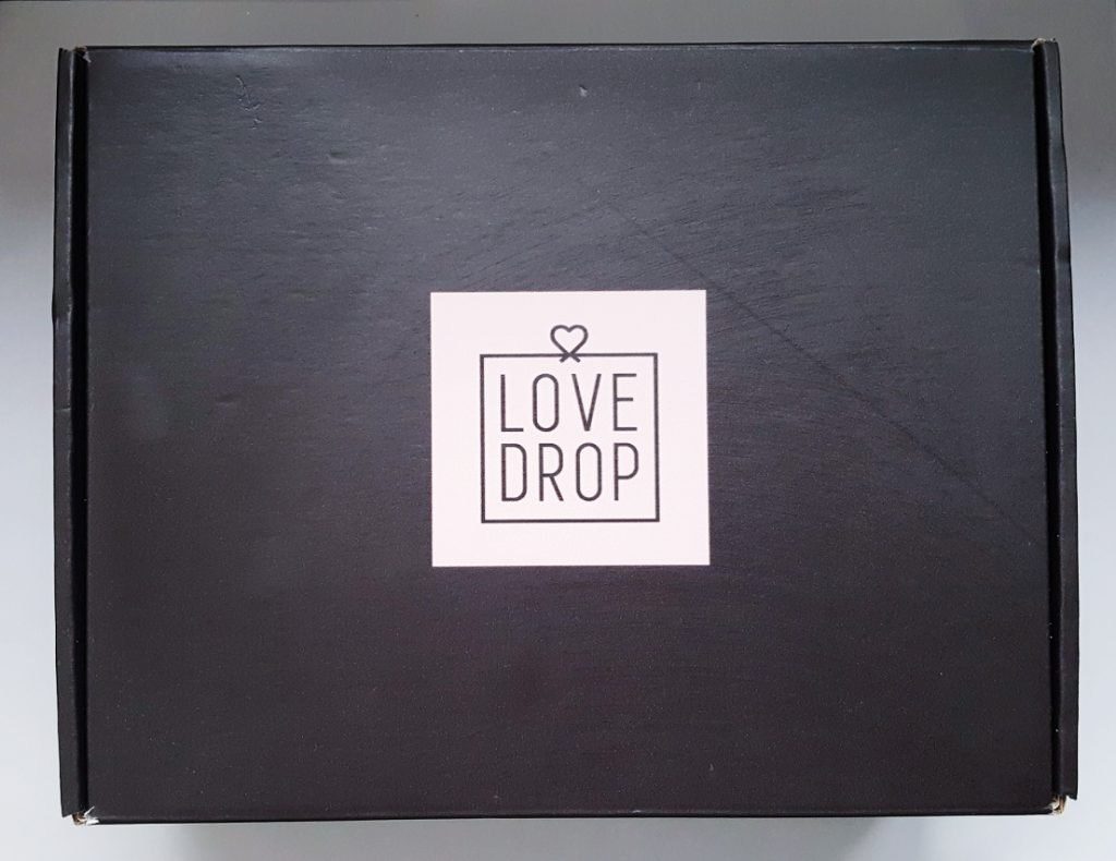 Photo of the Love Drop box. A black cardboard box with a pale pink Lovedrop logo.