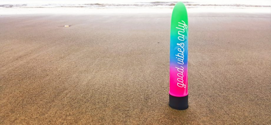Photo of a brightly colourd vibrator saying'Good Vibes Only' on the sand of a beach.
