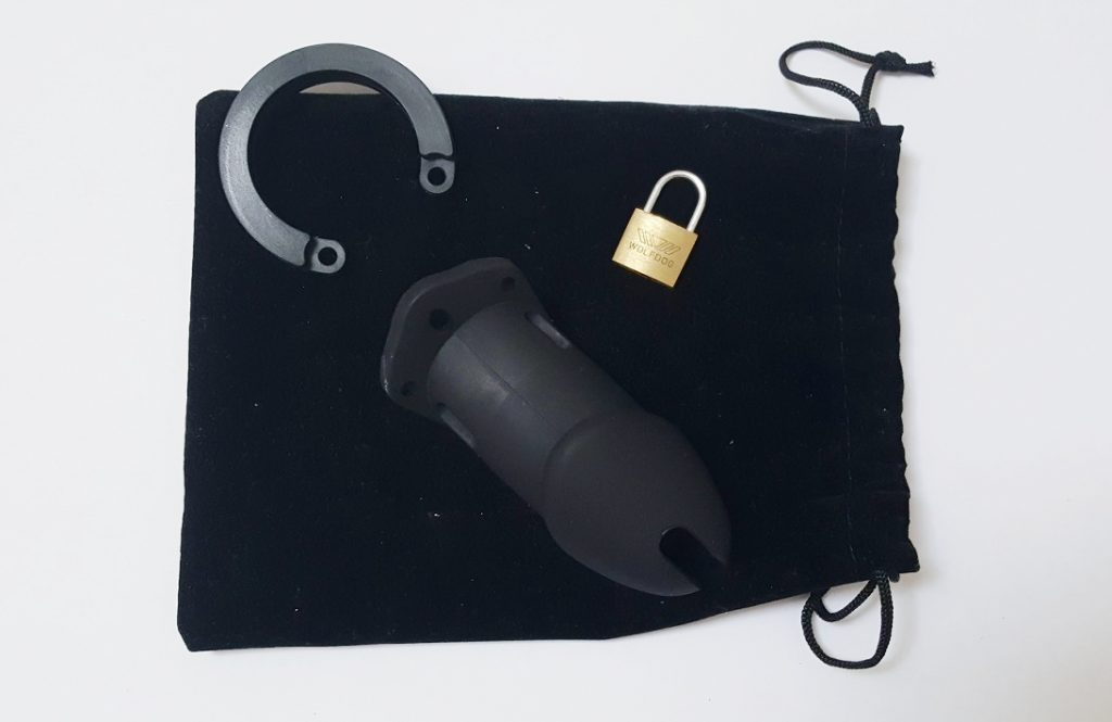 Image of the black velvet drawstring storage pouch with chastity device on top.