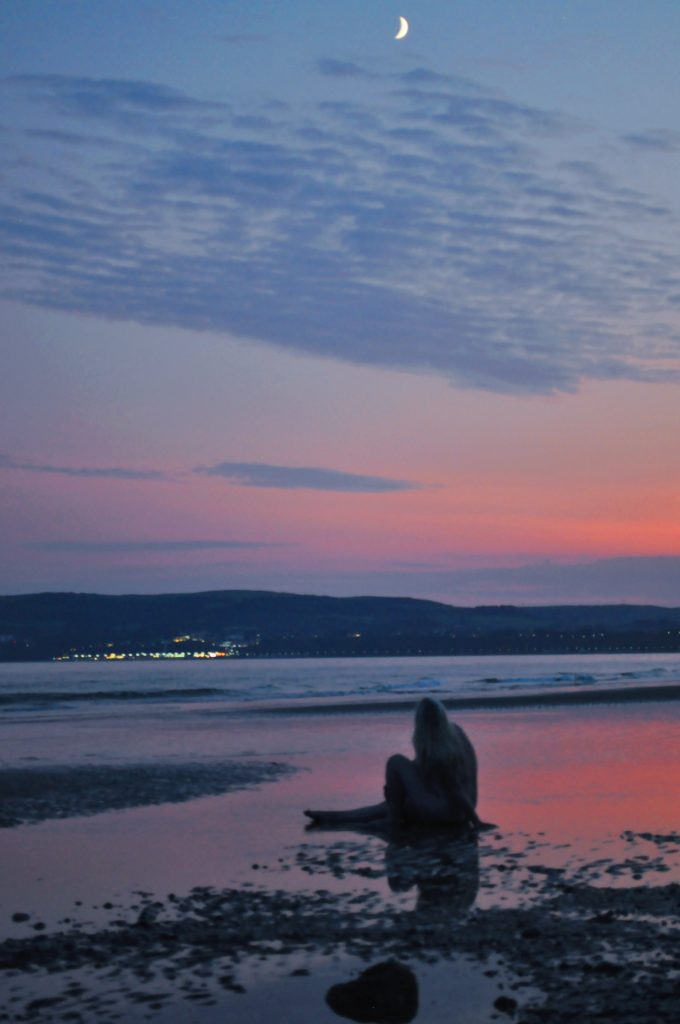 Photo taken in the early evening on a sea front. Aurora Glory posing naked on the beach with the tide out.
