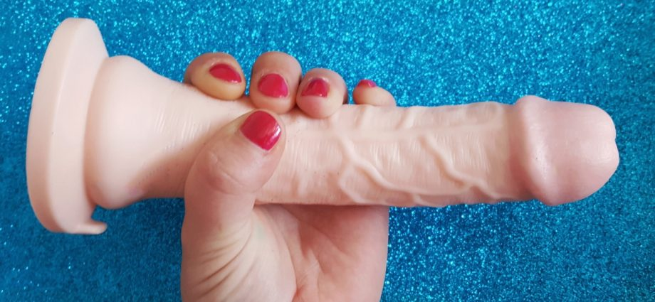 "Feature photo for Lovehoney Lifelike Lover Ultra Realistic 7"" Dildo review. Holding dildo over glittery blue background."