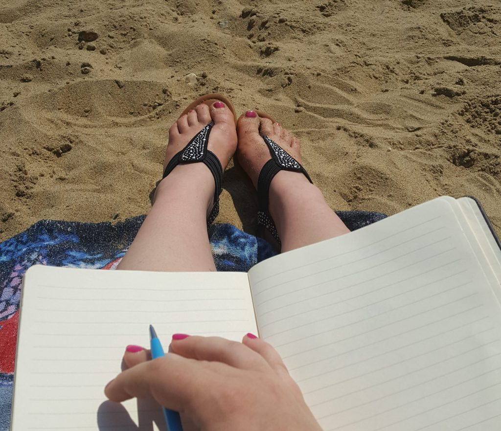 Photo of me holding a pen over a plain notebook. Sat on a towel with sparkly sandals on the beach.