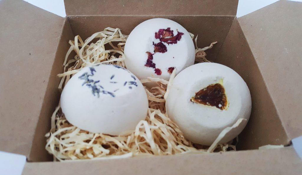 Photo of the GK Natural Creations - Bath Truffle Selection. Thre bath bombs in a cradboard box with wood curls.