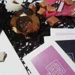 Feature photo for the April/May LoveDrop Subscription Box review. Image shows all included items on top of black curled paper.