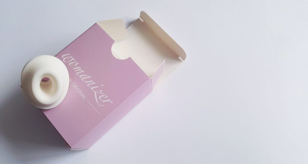 Image of a Womanizer Premium Smart Clitoral Stimulator Nozzle, on top of small cardboard box it arrives in.