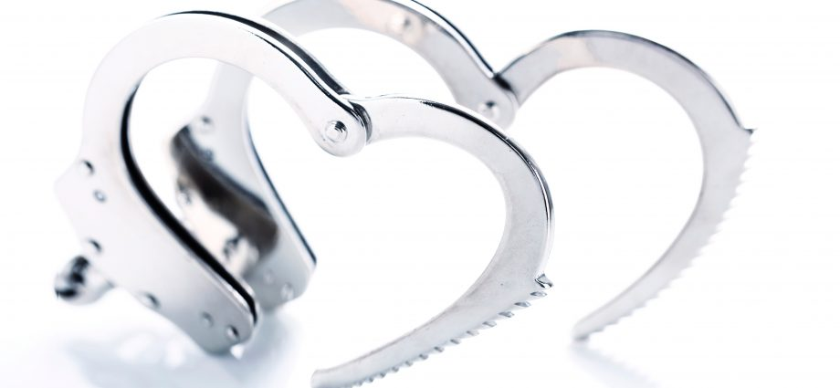 Photo of open metal handcuffs, each creating a heart shape