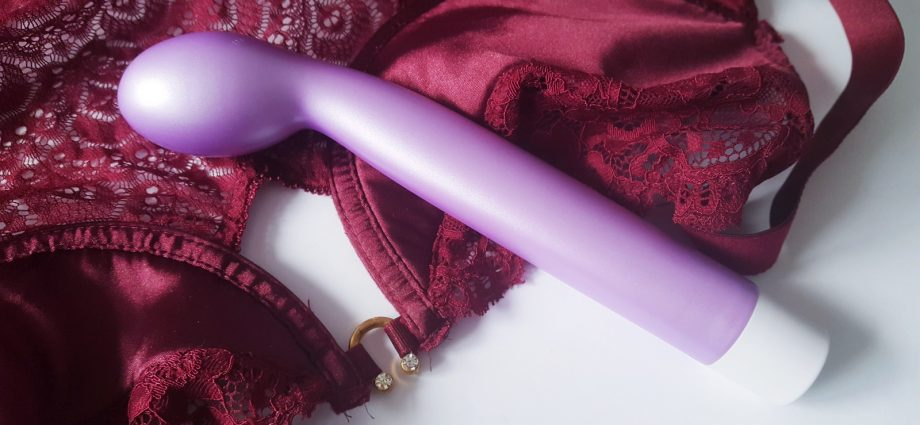 Feature photo for Blush Novelties Noje G Slim Vibrator review. Vibrator is laying over aubergine lace and satin lingerie.