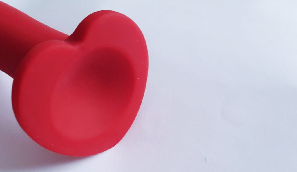 Close up photo of the Blush Novelties Temptasia Jezebel Dildo's Suction Cup. A heart shaped base with a circular indent.