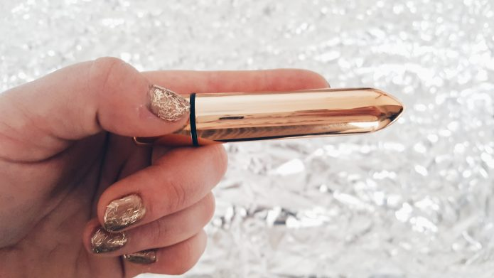 Feature photo for the Lovehoney Merry Kissmas Bullet Vibrator Review. Image of hand with gold nails, holding the vibrator over a shiny silver background.