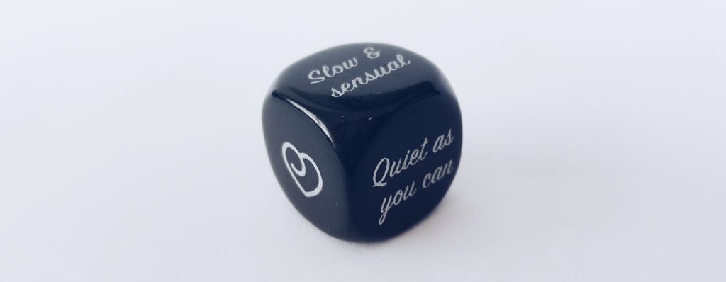 Image of the Lovehoney All Nighter Couples' Christmas Crackers Black Dice. Showing the side with Lovehoney logo, a side saying 'Qiet as you can' and another saying 'slow and sensual'.