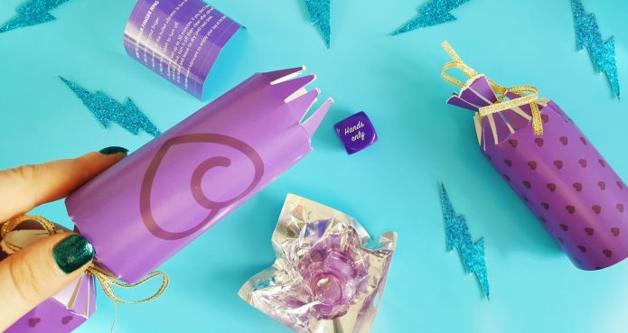 Feature photo for Lovehoney All Nighter Couples' Christmas Crackers Review. An image of the cracker open with the contents on blue background, including glittery blue lightning bolt images.