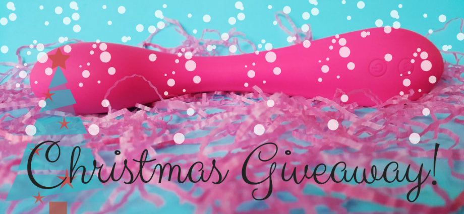 Feature photo for Aurora's Christmas Sex Toy Giveaway. An image of the Naught Passion G Spot Curve Vibrator on a blue background with pink paper confetti under and in front of the vibrator. Image has white snowflake dots over it and a blue clipart christmas tree in left bottom corner. It also has 'Christmas Giveaway' written across bottom of image.