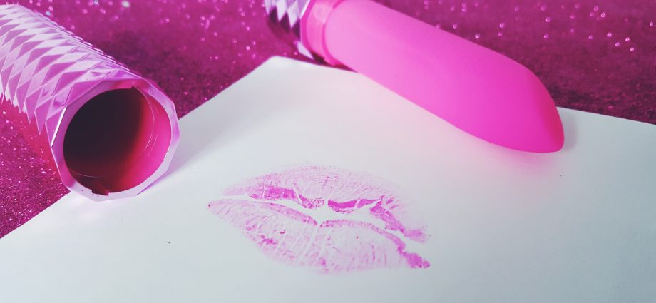 Feature image for the Maia Roxie Crystal Gem Lipstick Vibrator Review. Picture shows the vibrator and its lid on a glittery pink background, with a piece of white paper with a bright pink lipstick kiss on it.
