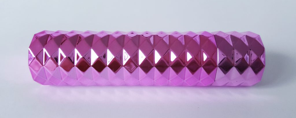 Image of the Maia Roxie Crystal Gem Lipstick Vibrator with its lid on. This only shows a cylindrical pink metallic exterior with triangular design.