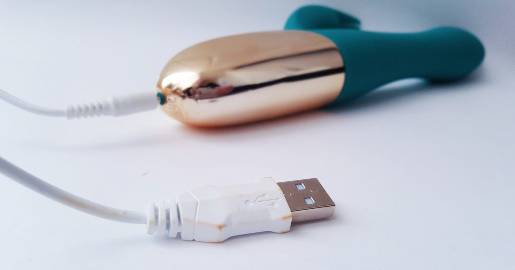 Image of the Maia Skyler Flexible Rabbit Vibrator with usb charger plugged into base.