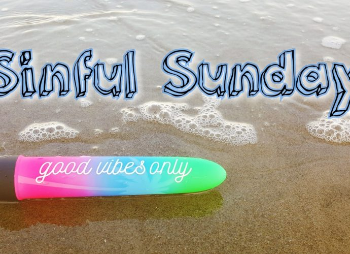 Photo of good vibe only vibrator on the beach with wave coming up to it. Photo says 'sinful sunday'