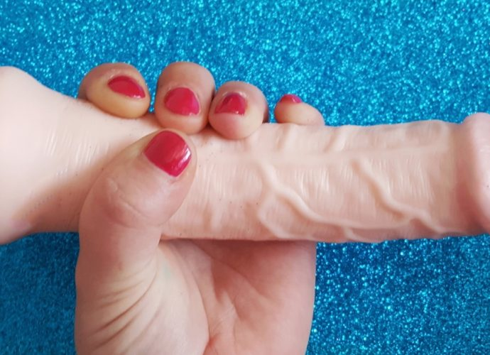 """Feature photo for Lovehoney Lifelike Lover Ultra Realistic 7"""" Dildo review. Holding dildo over glittery blue background."""