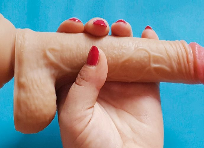 Feature photo for the Paloqueth Dual Density Dildo review. Hand holding the dildo over a blue background.