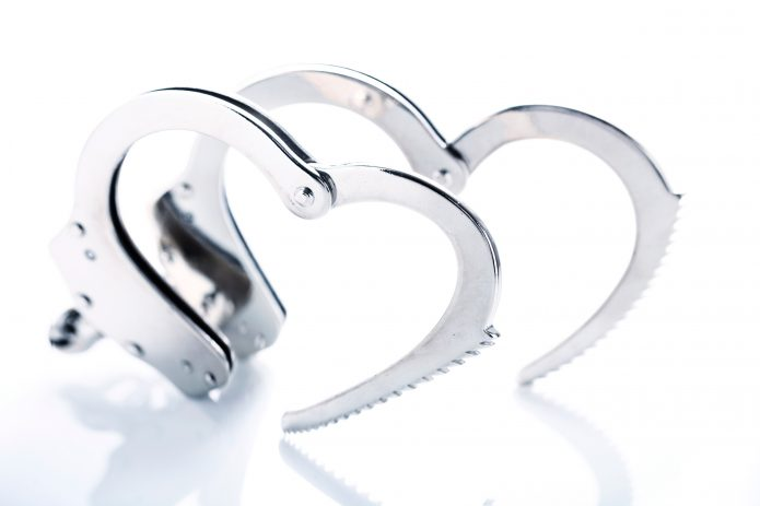 Photo of open metal handcuffs, each creating a heart shape