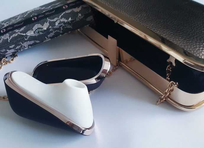 Feature photo for Satisfyer Pro Traveller Review. Satisfyer Traveller with a gold clutch bag and lace eyeshadow pallet.