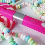 Feature photo for So Divine Get Lucky Review. Clitoral vibrator laid over large pink and white lollipop and multicoloured necklace sweeties.
