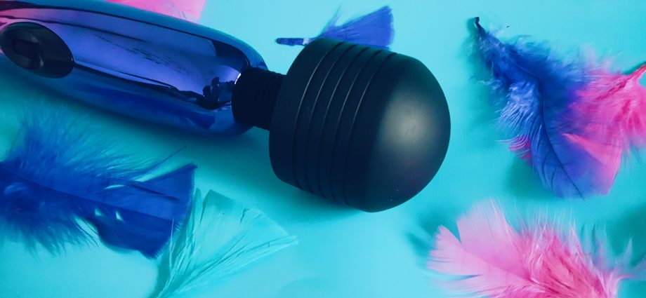 Feature image for Lovehoney Classic Metallic Magic Wand. An image of the vibrator laid over a blue background with coloured feathers around it.